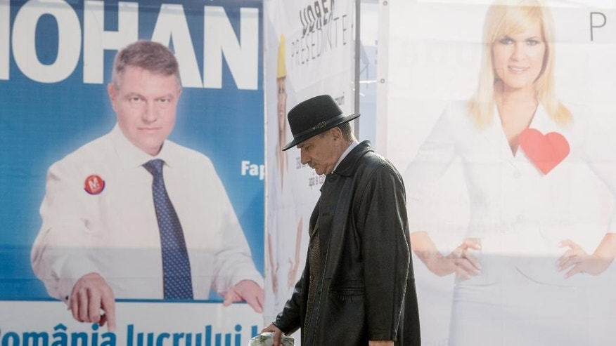 A man walks past campaign posters in Bucharest, Romania, Friday, Oct. 31, 2014. Romanians go to the polls on Sunday to elect a new leader as President Traian Basescu steps down after 10 years. (AP Photo/Andreea Alexandru, Mediafax) ROMANIA OUT