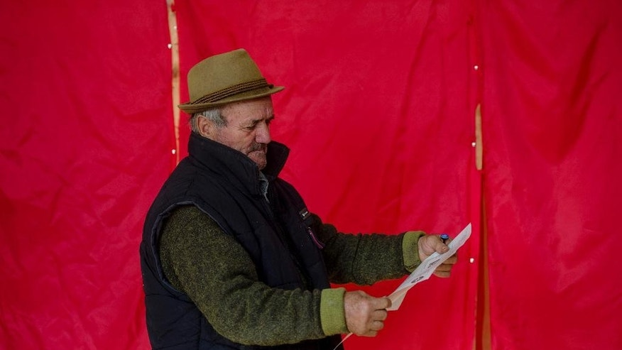 An elderly man reads a voting ballot paper in front of voting booths in the village of Branisteni some 35 kilometers from Bucharest, Romania, Sunday, Nov. 2, 2014. Romanians vote in the first round of the presidential elections, to elect a new leader as President Traian Basescu steps down after 10-years in office. (AP Photo/Andreea Alexandru, Mediafax) ROMANIA OUT