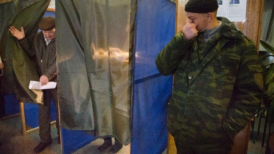 Nov. 2, 2014: A pro-Russian rebel stands guard as a man leaves a voting cabin at a polling station during supreme council and presidential elections in the city of Donetsk, eastern Ukraine. (AP)