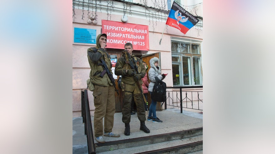 Pro-Russian rebels stand guard at a polling station during supreme council and presidential elections in the city of Donetsk, eastern Ukraine Sunday, Nov. 2, 2014. The pro-Russian rebels are holding the elections that were dismissed by Ukraine and the West as illegitimate. (AP Photo/Dmitry Lovetsky)