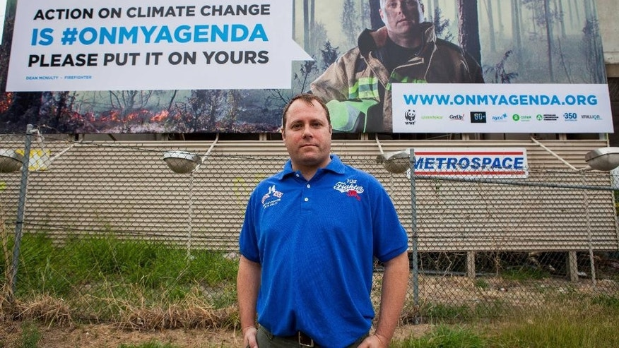 In this Nov. 3, 2014 photo provided by the World Wildlife Fund, firefighter Dean McNulty poses in front of a billboard on which he features, in Brisbane, Australia, that asks leaders of wealthy and developing countries to put climate change on the agenda of their G20 summit next week. Brisbane airport authorities have ruled that advertising billboards that oppose corruption and highlight climate change are too political to confront world leaders as they gather in the Australian city for a major economic summit. (AP Photo/World Wildlife Fund)