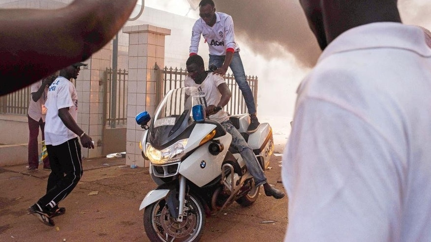 "In this photo taken Thursday, Oct. 30, 2014,  protestors steal a police motorbike outside the parliament building in Burkina Faso as they protest against their longtime president Blaise Compaore in the city of  Ouagadougou, Burkina Faso. Burkina Faso's military says it will hand over to a transitional government under a leader chosen by all sectors of society, to fill the power vacuum since long-time president Blaise Compaore resigned and fled. Lt. Col. Isaac Yacouba Zida met with diplomats Monday, Nov. 3, 2014, and announced the country will be led by ""a transitional body within the constitutional framework."" (AP Photo/Theo Renaut)"