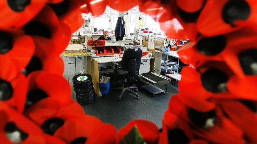 A view through a poppy wreath of the workroom at the Poppy Factory in Richmond near London, Thursday, Sept. 25, 2014. The factory makes the bulk of the 45 million poppies, wreaths and crosses sold across Britain to this day. (AP Photo/Kirsty Wigglesworth)