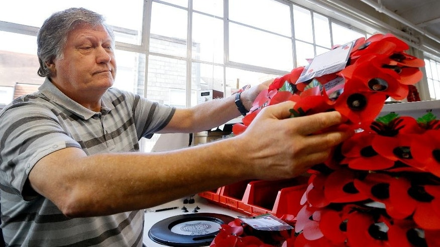 William Sellick, a former soldier in the Royal Green Jackets, who served in Northern Ireland, constructs poppy wreaths at the Poppy Factory in Richmond near London, Thursday, Sept. 25, 2014. With a practiced hand the 65-year-old veteran pinches two fabric petals, shapes them into a miniature flower, and attaches that to a wreath mold. Sellick, who suffered combat stress after an army tour to Northern Ireland in the 1970's finds making the wreaths a way to move on from a life shadowed by depression and alcoholism. (AP Photo/Kirsty Wigglesworth)