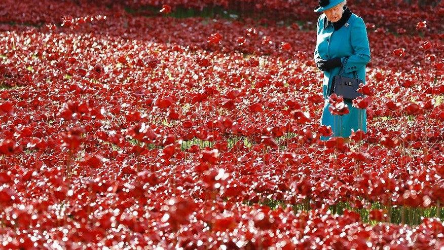 "FILE - In this Thursday, Oct. 16, 2014 file photo, Britain's Queen Elizabeth II walks through a field of ceramic poppies at The Tower of London. This year, the centenary of WWI, the poppy is more ubiquitous than ever. At the Tower of London, a sprawling crimson sea of ceramic flowers flood the ancient moat in a stunning display titled ""Blood Swept Lands and Sea of Red"". A total of 888,426 ceramic poppies, each representing a British soldier who died during the war, are planted over the summer, with the last one placed on Nov. 11, Armistice Day.  (AP Photo/Kirsty Wigglesworth, File)"