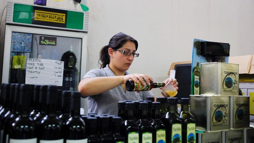 In this Tuesday, Oct. 28, 2014 photo, a woman works at Palestinian Taybeh brewery in Taybeh, West Bank. A tiny Christian enclave in the overwhelmingly Muslim West Bank has for years crafted the only Palestinian beer and brought thousands of visitors flocking to its annual beer fest. Now, it is adding wine to its list of libations, hoping a boutique winery will be another tourist draw and contribute to keeping the small village afloat. (AP Photo/Nasser Shiyoukhi)
