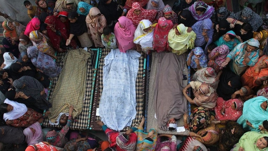 Pakistani women gather around the bodies of their relatives who were killed in a Sunday suicide bombing, Monday, Nov. 3, 2014 in Lahore, Pakistan. The suicide bomber detonated explosives close to a Pakistani paramilitary checkpoint near the country's eastern border with India, that killed more than 50 people in the deadliest attack to hit the country in several months, police and government officers said. (AP Photo/K.M. Chaudary)
