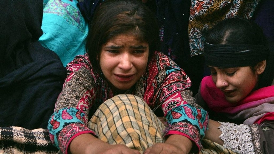 A Pakistani girl, Toba Ali, center, mourns next to the lifeless body of her father, who was killed in a Sunday suicide bombing, in Lahore, Pakistan, Monday, Nov. 3, 2014. The suicide bomber detonated explosives close to a Pakistani paramilitary checkpoint near the country's eastern border with India, that killed more than 50 people in the deadliest attack to hit the country in several months, police and government officers said. (AP Photo/K.M. Chaudary)