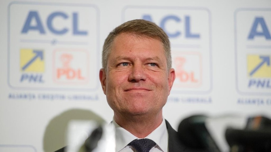 Klaus Iohannis, leader of Romania's centre-right Liberals and mayor of the Transylvanian city of Sibiu reacts upon seeing exit polls in Bucharest, Romania, Sunday, Nov. 2, 2014. Romanians voted in the first round of the presidential elections. According to exit polls Prime Minister Victor Ponta leads after the first round followed by Romania's centre-right Liberals candidate Klaus Iohannis. An election runoff will be held on Nov. 16. (AP Photo/Andreea Alexandru, Mediafax) ROMANIA OUT