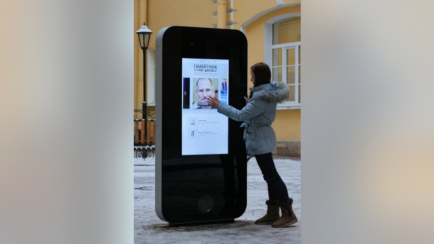 FILE- In this file photo dated Thursday, Jan. 10, 2013, a girl touches the screen showing a portrait of Steve Jobs on the recently erected memorial to late Apple Corp. co-founder in the courtyard of the Techno Park of the St. Petersburg National Research University of Information Technologies, Mechanics and Optics (ITMO University) in St. Petersburg, Russia.  The six-foot tall interactive memorial has been taken down in response to last week's announcement that CEO of Apple, Tim Cook is openly gay. (AP Photo/Dmitry Lovetsky, FILE )
