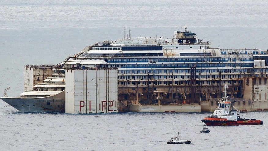 July 27, 2014 - FILE photo of tug boats towing the Costa Concordia ship outside Genoa's port, in northern Italy, where the ship is being broken up for scrap. The company dismantling the ship says workers have discovered human remains believed to be that of the last missing crew member.