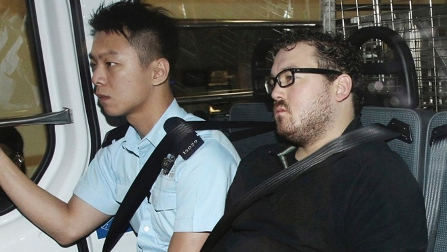 Nov. 3, 2014: Rurik George Caton Jutting, right, is escorted by a police officer in an police van before appearing in a court in Hong Kong.