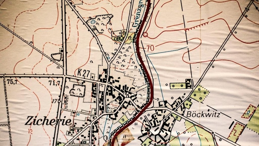 In this picture taken Oct 29, 2014 the red marked border between West and East Germany that runs through  the towns of  Boeckwitz and Zicherie photographed from a historic map  at the Wall Museum  in Boeckwitz, Germany. It was 1952, and East German authorities were erecting the wooden barrier that broke up the twin towns of Zicherie in the capitalist West and Boeckwitz in the communist East. The two had operated as one for centuries, sharing markets, schools and social clubs, and had long been the site of the Lenz family farm. Nearly a decade before the Berlin Wall went up, East Germany had already started sealing off its main frontier with West Germany, spanning nearly 1,400 kilometers (870 miles), dividing communities and even families.  (AP Photo/Markus Schreiber)