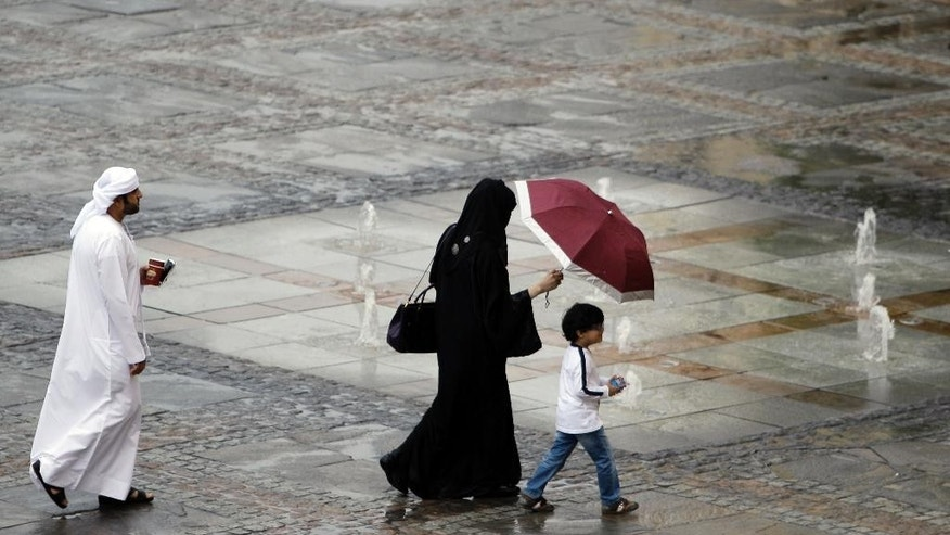 "In this Saturday, April 27, 2013 photo, an Emirati family enjoy walking after the rain was stopped at ""The Walk"" of the Jumeirah Beach Residence in Dubai, United Arab Emirates. Although the UAE is one of the wealthiest countries in the region, the gap between its richest families and everyone else is vast. But the UAE's rulers have long managed to establish political loyalty, maintain social stability and defuse potential unrest by instituting a number of lavish welfare programs including cushy pension funds and freedom from income tax. The result is a vast swath of people who rely on the government for jobs and benefits to maintain their lifestyles. (AP Photo/Kamran Jebreili)"