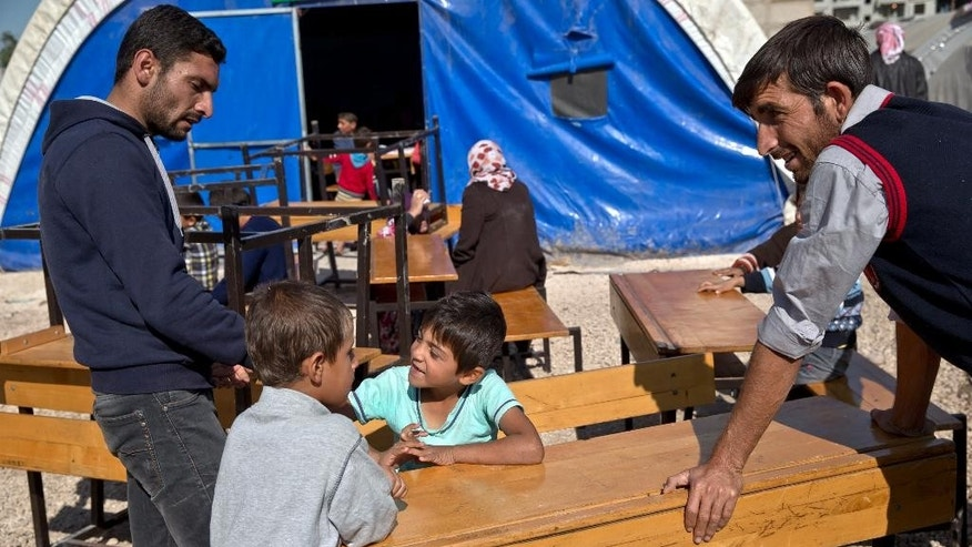 In this picture taken Sunday, Nov. 2, 2014, Syrian Kurdish refugee children from the Kobani area wait sitting at desks for the opening of a makeshift school at a refugee camp in Suruc, near the Turkey-Syria border. It's only a blue tent at the back of a refugee camp in the Turkish border town of Suruc. But for dozens of children who study in the makeshift school, it's a glimmer of hope. Inside, brightly colored drawings are pinned to the plastic walls, and wooden desks stand in two neat rows. For some of the Kurdish kids who fled with their families from the besieged Syrian town of Kobani across the border, this is the only school they've known. (AP Photo/Vadim Ghirda)