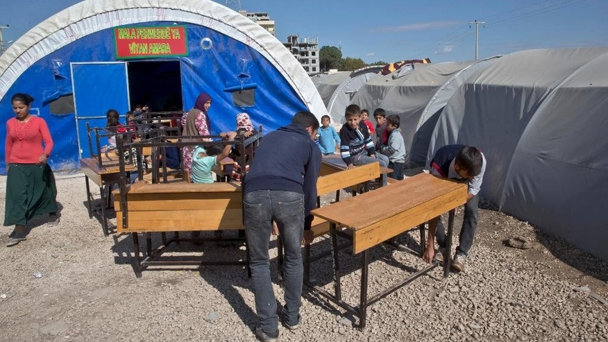 In this picture taken Sunday, Nov. 2, 2014, Syrian Kurdish refugee men from the Kobani area handle desks before the opening of a makeshift school, seen in the background, at a refugee camp in Suruc, near the Turkey-Syria border. It's only a blue tent at the back of a refugee camp in the Turkish border town of Suruc. But for dozens of children who study in the makeshift school, it's a glimmer of hope. Inside, brightly colored drawings are pinned to the plastic walls, and wooden desks stand in two neat rows. For some of the Kurdish kids who fled with their families from the besieged Syrian town of Kobani across the border, this is the only school they've known. (AP Photo/Vadim Ghirda)
