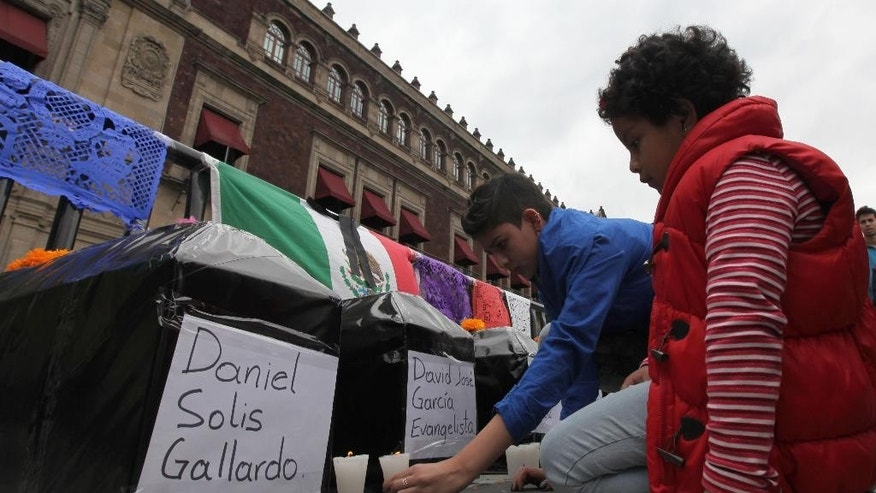 Children place candles next to six mock coffins, representing those who died in a police attack in Guerrero state, placed outside the National Palace by protesters in Mexico City, Saturday, Nov. 1, 2014. Relatives of the missing have grown increasingly frustrated at the pace of the investigation of the Sept. 26 police attack in the city of Iguala, that left six dead and 43 missing students. The missing were apparently handed over to a drug gang by city police. (AP Photo/Marco Ugarte)