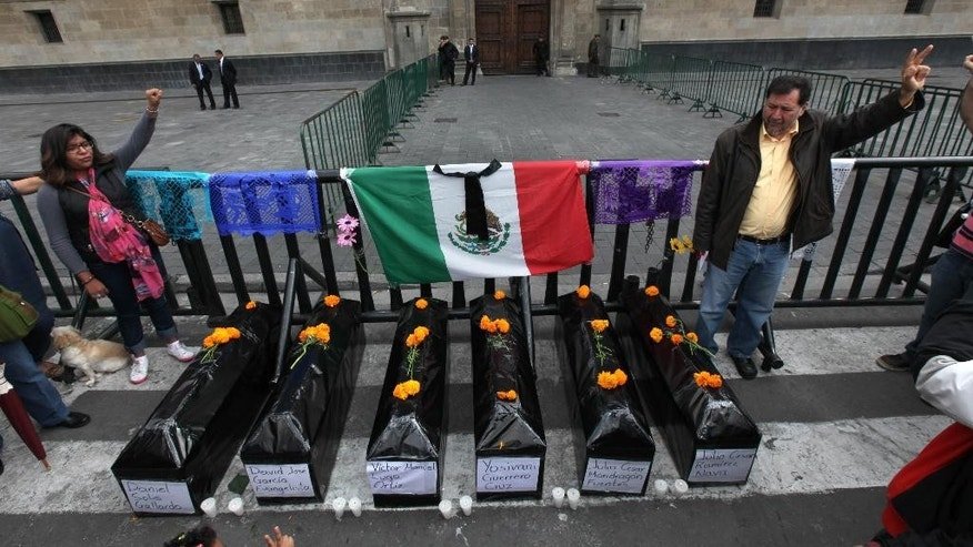 Protesters stand next to six mock coffins, representing those who died in a police attack in Guerrero state, as they demonstrate outside the National Palace in Mexico City, Saturday, Nov. 1, 2014. Relatives of the missing have grown increasingly frustrated at the pace of the investigation of the Sept. 26 police attack in the city of Iguala, that left six dead and 43 missing students. The missing were apparently handed over to a drug gang by city police. (AP Photo/Marco Ugarte)