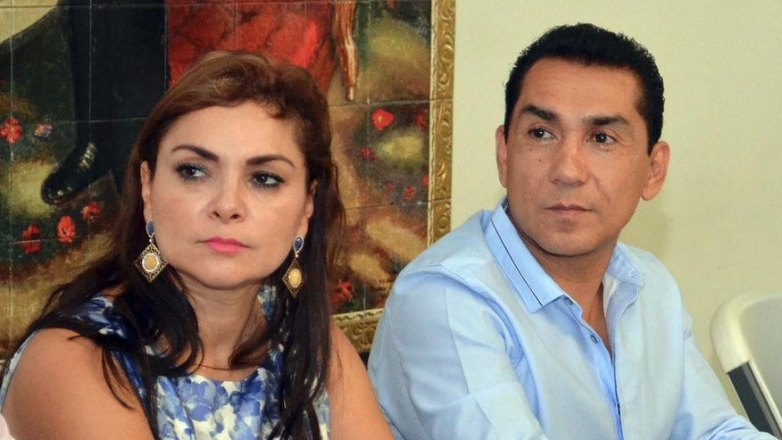FILE - In this May 8, 2014 file photo, the mayor of the city of Iguala, Jose Luis Abarca, right, and his wife Maria de los Angeles Pineda Villa meet with state government officials in Chilpancingo, Mexico. Federal police early Tuesday, Nov. 4, 2014 detained the couple, who are accused of ordering the Sept. 26 attacks on teachers' college students that left six dead and 43 still missing. The Iguala police chief is still a fugitive. (AP Photo/Alejandrino Gonzalez, File)