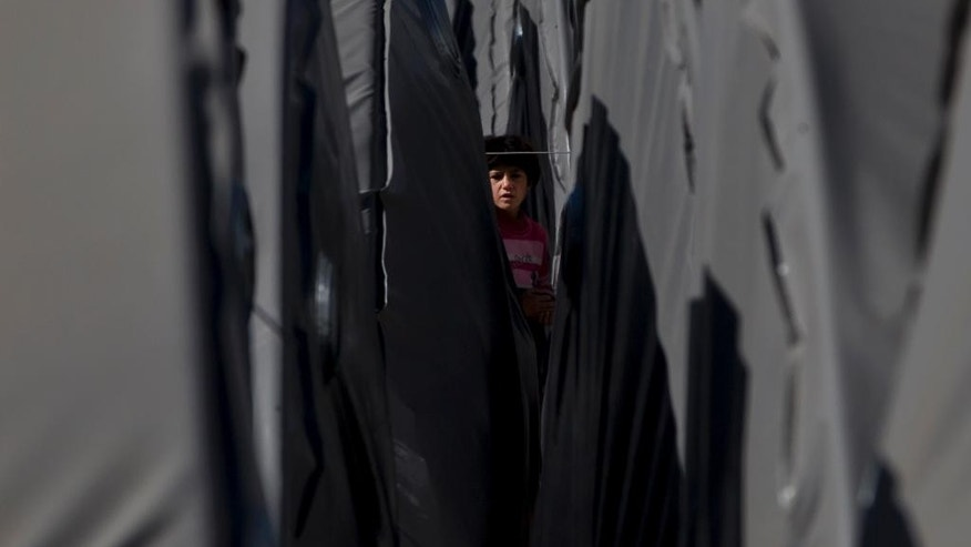 A Syrian Kurdish refugee child from Kobani walks between tents at a refugee camp in Suruc, near the Turkey-Syria border Monday, Nov. 3, 2014. Kobani, also known as Ayn Arab, and its surrounding areas, has been under assault by extremists of the Islamic State group since mid-September and is being defended by Kurdish fighters. (AP Photo/Vadim Ghirda)