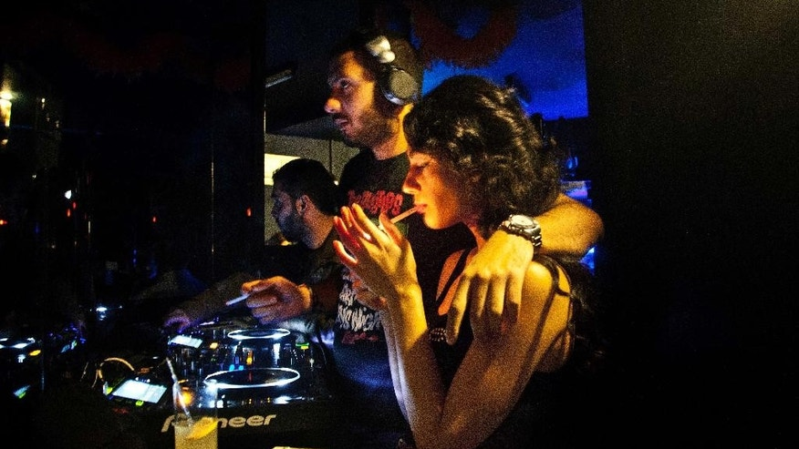 In this Thursday, Oct. 30, 2014 photo, a woman lights up a cigarette in the DJ booth at a Halloween party in an upscale Damascus hotel, Syria. Followed by a vampire and a medieval knight, a man dressed up as an Islamic militant walks into the thumping club, past the blue-lit bar in a Damascus hotel, determined to party. The music is pounding, a break-dancer stands on his head and in the DJ booth, a man and woman are kissing. (AP Photo/Diaa Hadid)