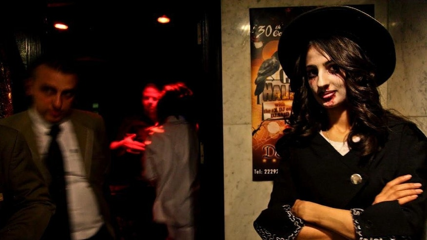 In this Thursday, Oct. 30, 2014 photo, a woman attends a Halloween party in an upscale Damascus hotel, Syria. Followed by a vampire and a medieval knight, a man dressed up as an Islamic militant walks into the thumping club, past the blue-lit bar in a Damascus hotel, determined to party. The music is pounding, a break-dancer stands on his head and in the DJ booth, a man and woman are kissing. (AP Photo/Diaa Hadid)