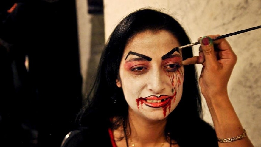In this Thursday, Oct. 30, 2014 photo, a woman gets her face painted before entering  a Halloween party in an upscale Damascus hotel, Syria. Amid a conflict grinding well into its fourth year, Syrians have sought to deny war its miserable monotony by taking pleasure in mindless entertainment, ranging from lounging in cafes, to dancing to thumping discos. (AP Photo/Diaa Hadid)