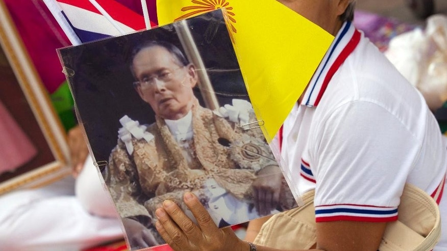 FILE - In this Sept. 15, 2014 file photo, a Thai woman holds a portrait of King Bhumibol Adulyadej at Siriraj Hospital in Bangkok where the Thai king received medical checkups before returning to his seaside palace. A Thai court sentenced a university student to 2 1/2 years in prison on Tuesday, Nov. 4 for posting a message on Facebook that the court said insulted the country's king. A Criminal Court judge found 24-year-old Akkaradet Eiamsuwan guilty of violating Thailand's lese majeste law, which punishes people who defame, insult or threaten the monarchy.  (AP Photo/Sakchai Lalit, File)