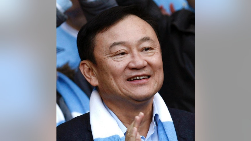 FILE - In this April 30, 2012 file photo, former Thailand's Prime Minister Thaksin Shinawatra takes his seat amongst supporters before an English Premier League soccer match in Manchester, England. Thailand's military-installed government appointed a committee on Tuesday, Nov. 4, 2014 to draft the country's new constitution amid speculation that it will seek to bar former Prime Minister Thaksin and his allies from politics. (AP Photo/Jon Super, File)