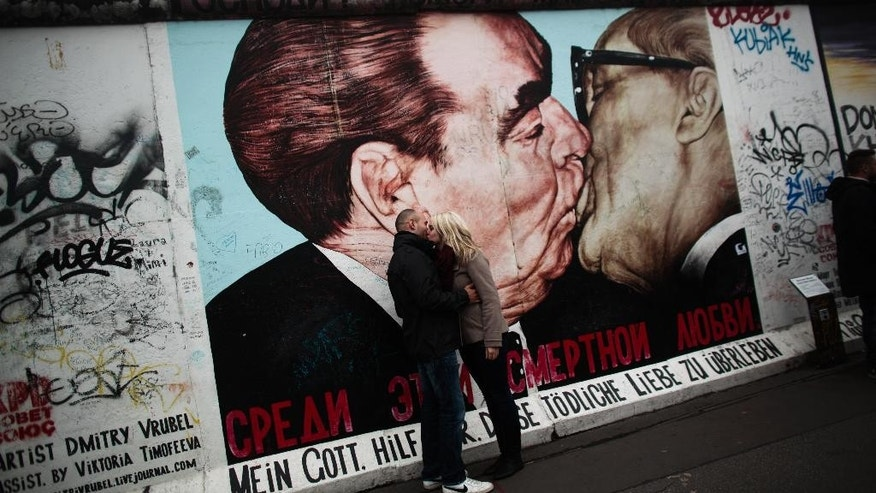 In this Oct. 30, 2014 photo a couple kiss in front of a painting of former Soviet leader Leonid Brezhnev, left, and long time East German communistic leader Erich Honecker at the East Side Gallery, the largest part of original remains of the Berlin Wall in Berlin. On Nov. 9, 2014, Germany celebrate the 25th anniversary of the fall of the wall on Nov. 9, 1989. After 25 years only a few remains of the wall remind of the about 160 kilometers (about 100 miles) long border which surrounded the west part of Berlin. The East Side gallery is a part of the Wall which separated East Berlin from the river Spree, where the border at this area was located. With 1300 meters it is the longest remaining part of the Berlin Wall. (AP Photo/Markus Schreiber)