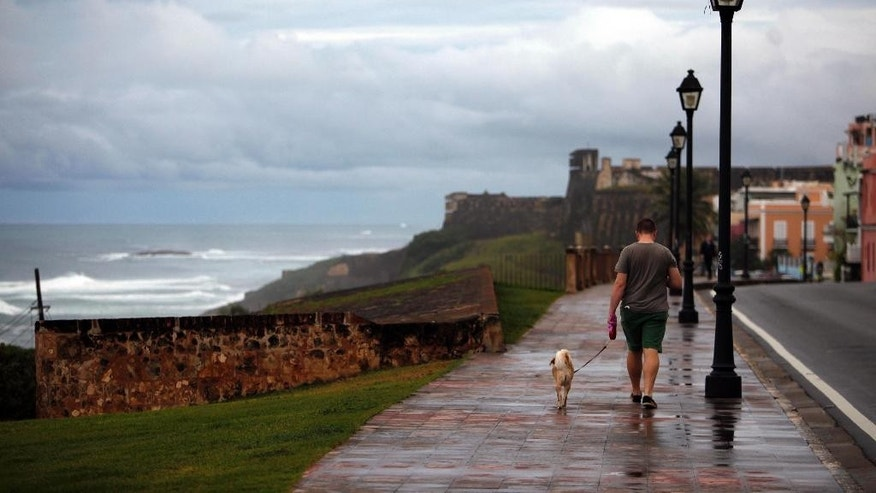 A man walks a dog during a rainy day in Old San Juan, Puerto Rico, Tuesday, Nov. 4, 2014. Heavy rains caused by a cluster of storms in the northern Caribbean killed at least seven people in Haiti and caused major flooding on Tuesday in the Dominican Republic and Puerto Rico, authorities said. (AP Photo/Ricardo Arduengo)