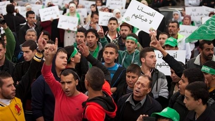 "Oct. 17, 2014: Palestinian supporters of the Islamist movement Hamas shout slogans and hold  pears with a slogan written in Arabic, ""our Al-Aqsa is not their temple,"" during a protest against Israeli restrictions at the Al-Aqsa Mosque, in the West Bank City of Ramallah."