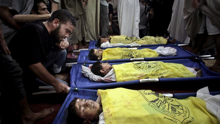 "FILE - In this Wednesday, July 16, 2014, file photo, Palestinians mourn over the lifeless bodies of four boys from the same extended Bakr family, covered with yellow flags of Fatah movement, in the mosque during their funeral in Gaza City.A leading human rights group has accused Israel of committing war crimes during this summer's war in Gaza. Amnesty International says Israel displayed ""callous indifference"" in attacks on family homes in the densely populated coastal strip that in some cases amounted to war crimes. (AP Photo/Khalil Hamra, File)"