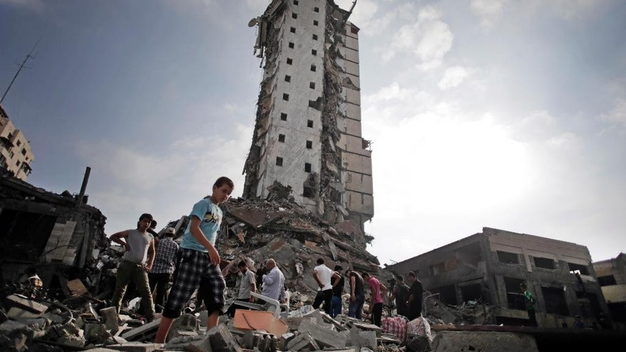 "FILE - In this Aug. 26, 2014 file photo, Palestinians inspect the damage to the Italian Complex following several late night Israeli airstrikes in Gaza City. A leading human rights group has accused Israel of committing war crimes during this summer's war in Gaza. Amnesty International says Israel displayed ""callous indifference"" in attacks on family homes in the densely populated coastal strip that in some cases amounted to war crimes. (AP Photo/Khalil Hamra, File)"