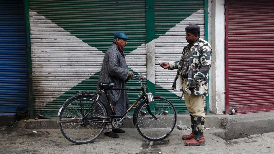 An Indian paramilitary soldier checks the identity of a civilian during curfew in Srinagar, India, Tuesday, Nov. 4, 2014. Parts of the city were under curfew after Indian army soldiers killed two Kashmiris at a check-point in Jammu and Kashmir's Budgam district on Monday. (AP Photo/Mukhtar Khan)