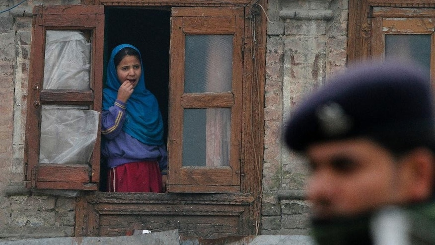 A Kashmiri girl watch from window of her house as an Indian paramilitary soldier guards during a curfew in Srinagar, Indian controlled Kashmir, Tuesday, Nov. 4, 2014. Parts of the city were under curfew after Indian army soldiers killed two Kashmiris at a check-point in Jammu and Kashmir's Budgam district on Monday. (AP Photo/Mukhtar Khan)