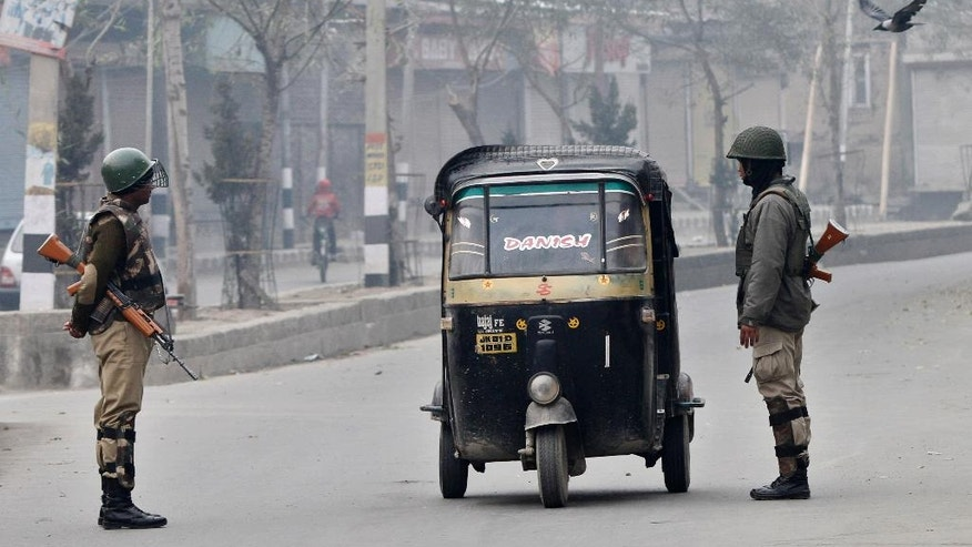 Indian paramilitary soldier interrogate civilians inside an autorickshaw at a temporary check point during curfew in Srinagar, India, Tuesday, Nov. 4, 2014. Parts of the city were under curfew after Indian army soldiers killed two Kashmiris at a check-point in Jammu and Kashmir's Budgam district on Monday. (AP Photo/Mukhtar Khan)