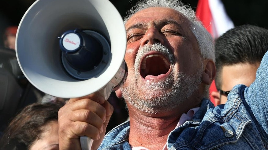A Lebanese activist holds a bullhorn as he shouts slogans against the Lebanese lawmakers during a protest against the extension of the parliament, on  a road that leads to the Parliament building, in downtown Beirut, Lebanon, Wednesday, Nov. 5, 2014. Demonstrators on Wednesday blocked roads leading to the parliament and threw tomatoes at lawmakers' cars. Lebanon's parliament is attempting to extend its own term in office by more than two years. But a group of protesters is trying to stop it. (AP Photo/Hussein Malla)