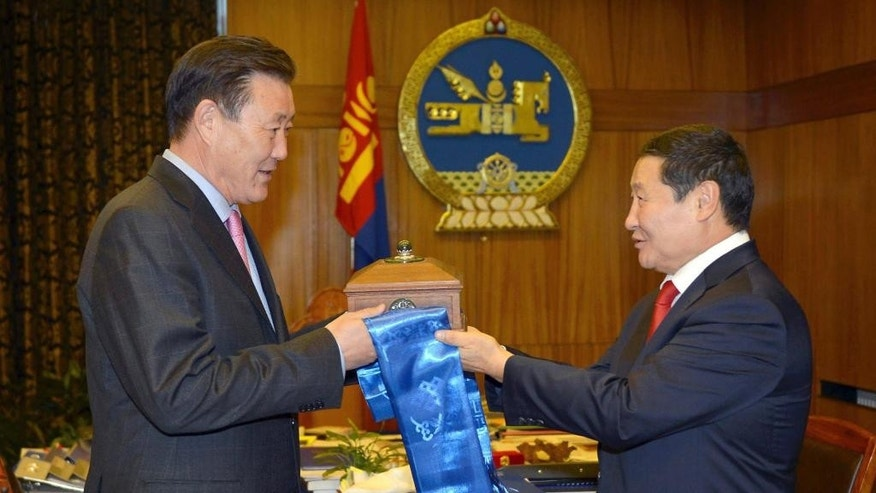 In this photo released by Press Service of the Government of Mongolia, Mongolian Prime Minister Altankhuyag Norov, right, hands over his official government seal to his senior deputy Terbishdagva Dendev who takes over as acting prime minister at the Mongolia government house in Ulan Bator, Mongolia Wednesday, Nov. 5, 2014. Mongolia's parliament voted Wednesday to dismiss the prime minister, who has been under fire for alleged corruption within his administration and who faced criticism for drastically slower economic growth. (AP Photo/Press Service of the Government of Mongolia)