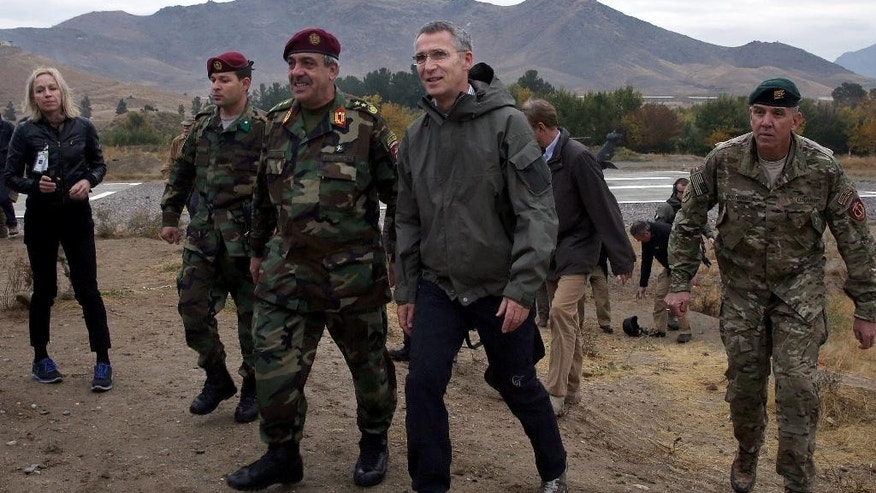 Secretary General of NATO, Jens Stoltenberg, center, walks with Afghanistan's National Army officials during his first visit as head of NATO at special forces training camp in Kabul, Afghanistan, Thursday, Nov. 6, 2014.  (AP Photo/Massoud Hossaini)