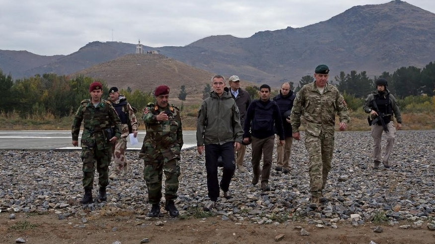 Secretary General of NATO, Jens Stoltenberg, center, walks with Afghanistan's National Army officials during his first visit as head of NATO at the special forces training camp in Kabul, Afghanistan, Thursday, Nov. 6, 2014. (AP Photo/Massoud Hossaini)