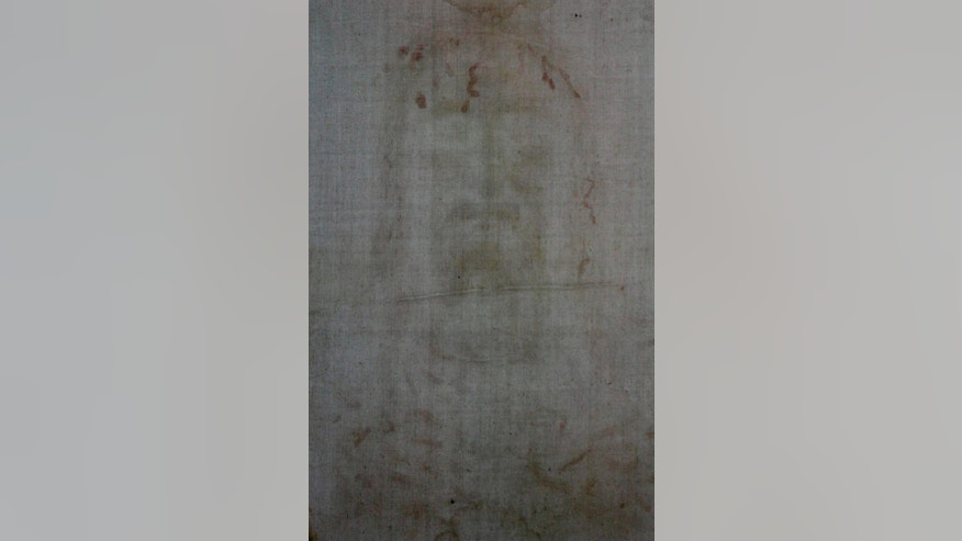 FILE -- In this file photo taken on April 10, 2010, the faded image of a bearded man appears on a detail of  The Holy Shroud, a 14 foot-long linen revered by some as the burial cloth of Jesus, at the Turin cathedral, Italy. The Shroud of Turin, the burial cloth some believe covered Jesus, will go back on public display next year. Pope Francis said Wednesday, Nov. 5, 2014, he will go to that northern Italian city June 21 to view that 4.3-meter-long (14-foot) cloth, which is kept in a climate-controlled case in Turin's cathedral. As during the last display in 2010, reservations are required for the April 19-June 24 viewing but there is no charge. (AP Photo/Luca Bruno)