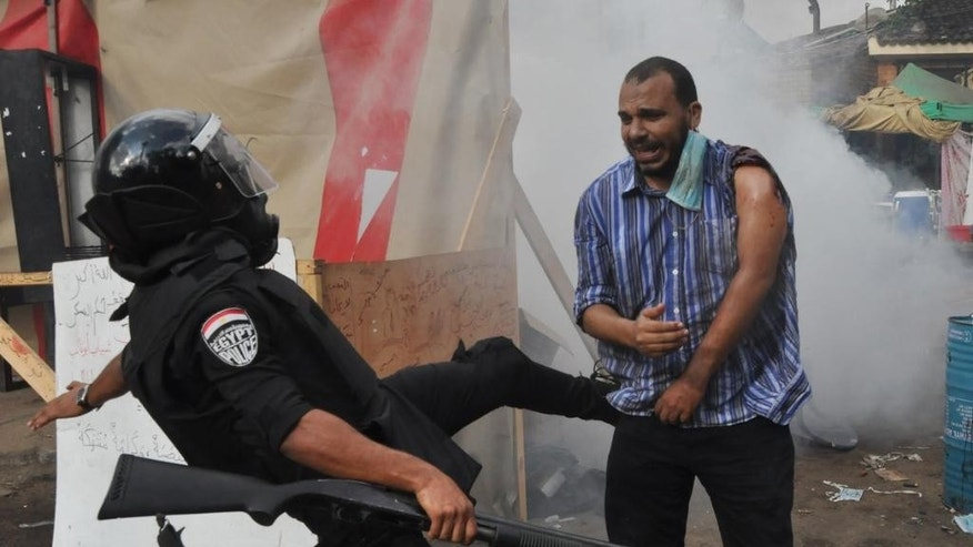 FILE - In this Wednesday, Aug. 14, 2013 file photo, a member of the Egyptian security forces kicks a supporter of ousted Islamist President Mohammed Morsi as they clear a sit-in camp set up near Cairo University in Cairo's Giza district, Egypt. The United States and other countries on Wednesday, Nov. 5, 2014 slammed the human rights situation in Egypt at a United Nations meeting reviewing the country's record for the first time since the 2011 ouster of longtime autocrat Hosni Mubarak. (AP Photo/Hussein Tallal, File)
