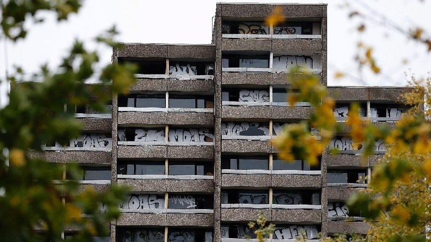 In this picture taken Nov. 3, 2014, a rundown empty tower block shows graffiti in Dortmund, Germany.  Twenty five years after the fall of the Berlin Wall, the disparities that remain between former West and East Germany are a common theme. Unemployment is higher in the east, disposable incomes are lower and the populations are older as the young move west for better opportunities. But the broad-brush look at unified Germany glosses over some major exceptions as Dresden and Dortmund.  (AP Photo/Frank Augstein)