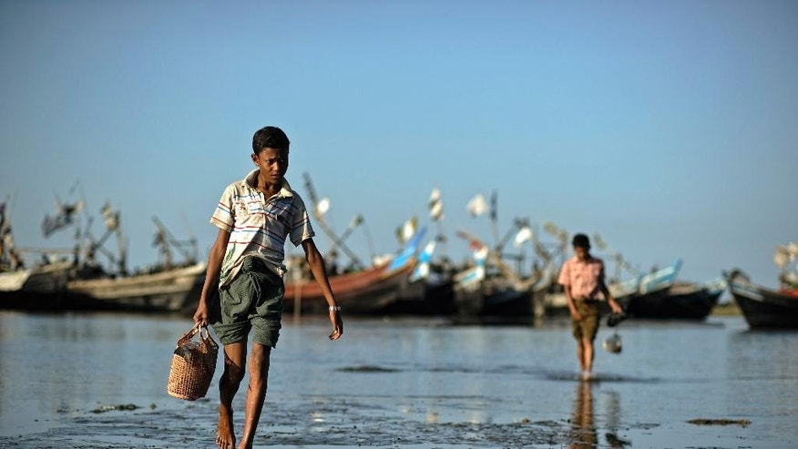 In this Nov. 29, 2013 photo, a Rohingya boy wades through the water carrying a basket of fish at The' Chaung refugee camp, on the outskirts of Sittwe, Myanmar. The small wooden boats leave the shores of western Myanmar nearly every day, overloaded with desperate Rohingya Muslims who are part of one the largest boat exoduses in Asia since the Vietnam War. Helping them on their way: Myanmar's own security forces, who are profiting off the mass departure of one of the world's most persecuted minorities by extracting payments from those fleeing. A report to be released Friday, Nov. 7, 2014, by the Bangkok-based advocacy group Fortify Rights, and reporting by The Associated Press, indicate the practice is far more widespread and organized than previously thought, with Myanmar naval boats going so far as to escort asylum seekers out sea, where larger ships operated by transnational criminal networks wait to pick them up. (AP Photo/Kaung Htet)