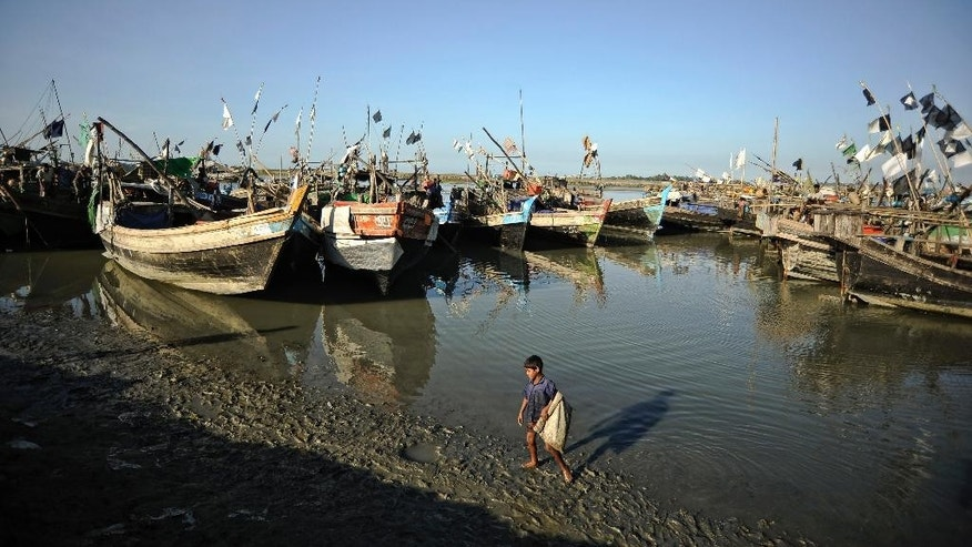 In this Nov. 29, 2013 photo, Rohingya fishing boats are docked at The Chaung refugee camp, on the outskirts of Sittwe, Myanmar. The small wooden boats leave the shores of western Myanmar nearly every day, overloaded with desperate Rohingya Muslims who are part of one the largest boat exoduses in Asia since the Vietnam War. Helping them on their way: Myanmar's own security forces, who are profiting off the mass departure of one of the world's most persecuted minorities by extracting payments from those fleeing. A report to be released Friday, Nov. 7, 2014, by the Bangkok-based advocacy group Fortify Rights, and reporting by The Associated Press, indicate the practice is far more widespread and organized than previously thought, with Myanmar naval boats going so far as to escort asylum seekers out sea, where larger ships operated by transnational criminal networks wait to pick them up. (AP Photo/Kaung Htet)