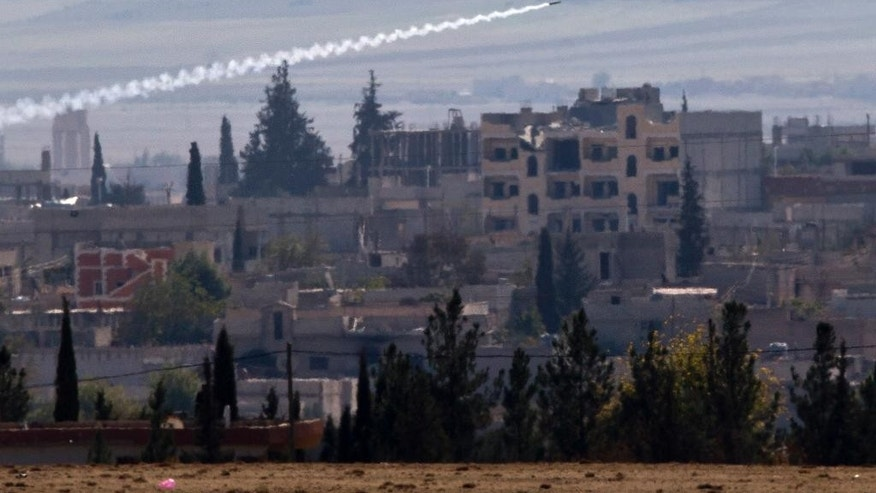 Nov. 6, 2014: A missile is fired from Islamic State positions in Kobani, seen from a hilltop outside Suruc, on the Turkey-Syria border. (AP)