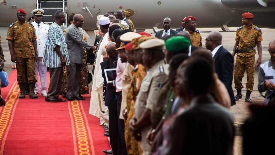 Ghana's President John Dramani Mahama, center rear, shake hands with people after arriving in  Burkina Faso, with Lt. Col. Issac Yacouba Zida,  left rear,  at the airport in Ouagadougou, Burkina Faso, Wednesday, Nov. 5, 2014. Diplomats pressing Burkina Faso's military ruler to return the country to civilian rule said Wednesday they are seeking names of people who could serve as interim head of state until elections are held. The announcement came after the presidents of Nigeria, Senegal and Ghana arrived in Burkina Faso for talks. (AP Photo/Theo Renaut)