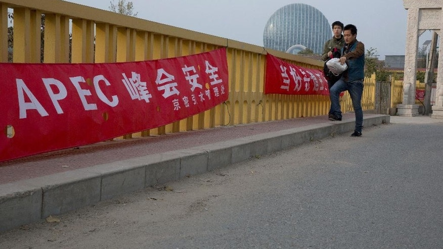 "In this photo taken Wednesday, Oct. 29, 2014, Chinese men walk past a banner with the words reading: ""APEC summit safety"" near the venue hotel in Beijing. China plans to use a meeting of Asia-Pacific leaders to promote a regional trade initiative at a time when progress on a rival U.S.-led trade deal has stalled, injecting a note of rivalry into the annual summit. (AP Photo/Ng Han Guan)"