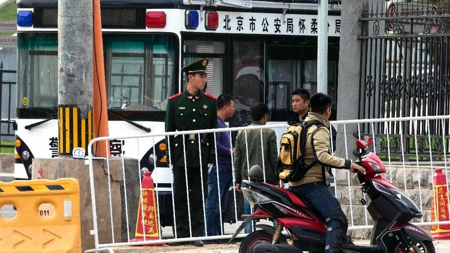 In this photo taken Wednesday, Oct. 29, 2014, a Chinese paramilitary policeman guards barriers sealing off a road to the venue for the upcoming APEC summit in the Huairou district of Beijing. China plans to use a meeting of Asia-Pacific leaders to promote a regional trade initiative at a time when progress on a rival U.S.-led trade deal has stalled, injecting a note of rivalry into the annual summit. (AP Photo/Ng Han Guan)